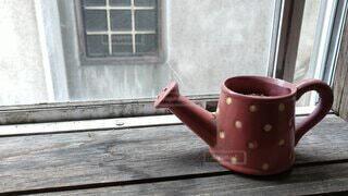 窓際のじょうろの形の植木鉢の写真・画像素材[4554476]