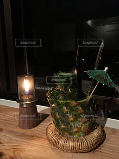 キャンドルの明かりで飲むパイナップルジュースの写真・画像素材[4563952]