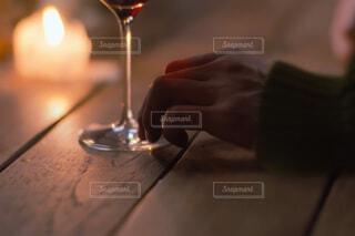 木製テーブルにワイングラスとキャンドルライトの写真・画像素材[4568791]