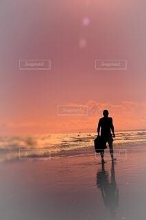 夕陽を浴びて砂浜を歩く男の写真・画像素材[4653040]