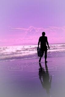 夕陽を浴びて砂浜を歩く男の写真・画像素材[4653038]