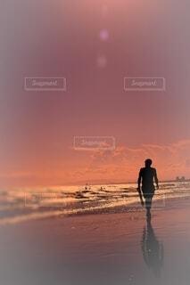 夕陽を浴びて砂浜を歩く男の写真・画像素材[4653039]