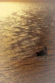 夕焼けの海に浮かぶ釣り船の写真・画像素材[4653062]