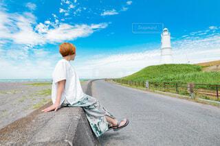 堤防に座って灯台を眺める女性の写真・画像素材[4584255]