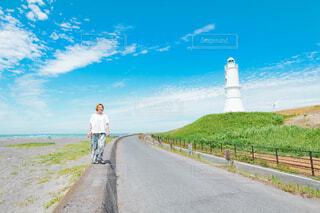 堤防を散歩する女性の写真・画像素材[4585475]