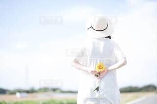 ひまわりを持っている女性の後ろ姿の写真・画像素材[4677086]