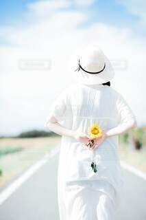 ひまわりを持つ女性の後ろ姿の写真・画像素材[4677087]