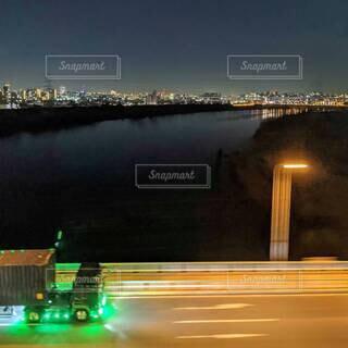 夜の川★橋の上を走る電飾トラックの写真・画像素材[4612096]