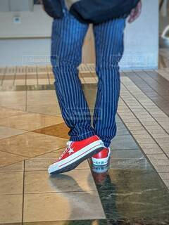 赤いスニーカーを履いて歩く男性の写真・画像素材[4637211]