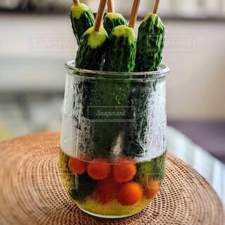 割り箸を刺した丸ごと胡瓜とプチトマトの甘酢漬け。の写真・画像素材[4695081]