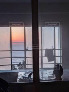 ホテルの部屋風呂で、朝焼けを眺めながらお湯に浸かる男性。の写真・画像素材[4729197]