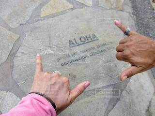 ハワイで石畳に刻まれたALOHAの刻印。シャカをする男女の手の写真・画像素材[4736656]