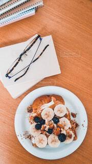 バナナトースト 文庫本の上に置かれた眼鏡の写真・画像素材[4784346]