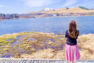 水の体の前で立っている女の子の写真・画像素材[1103605]
