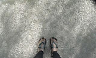 透き通った海の浅瀬にビーチサンダルで立っているの写真・画像素材[4647124]