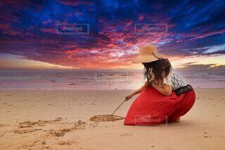 女性,1人,海,夕日,綺麗,後ろ姿,砂浜,帽子,散歩,観光地,ハート,人物,浜辺,ロングヘアー,夕景,マジックアワー,佇む,ニット,描く,海水浴場,ブラウス,赤いスカート