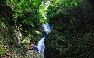 女性,1人,自然,絶景,屋外,緑,後ろ姿,ジーンズ,水面,景色,滝,観光,樹木,岩,新緑,渓谷,渓流,流れ,巨大,ヒーリング,セラピー,眺める,落差