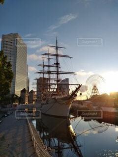 朝日を背にした日本丸と鏡のような水面の写真・画像素材[4664862]