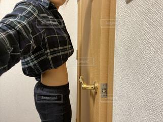 ドアの隣に立っている若い男の子の写真・画像素材[2807918]