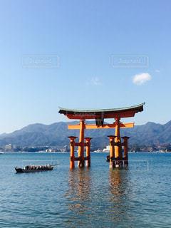 背景の山と水の体のボートの写真・画像素材[1195690]
