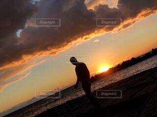 夕日の前に立つ男性の写真・画像素材[4694236]