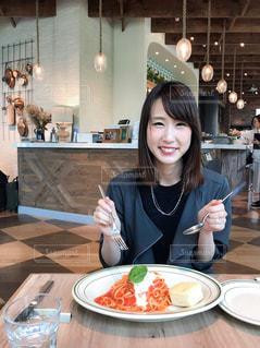 食品のプレートをテーブルに座っている女性の写真・画像素材[737819]