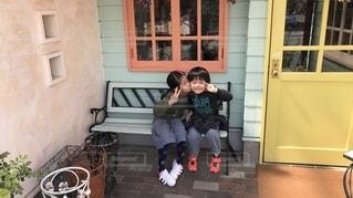 建物の前にあるベンチに座っている小さな子供の写真・画像素材[1161599]