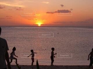 夕暮れ時に海辺で遊ぶ子供たちの写真・画像素材[4787443]
