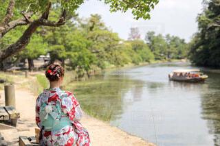 川のほとりに座ってる女性の写真・画像素材[4776061]