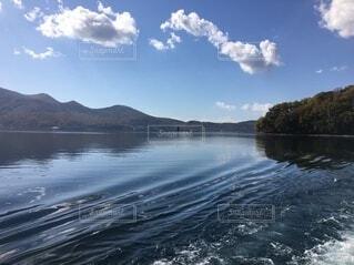 揺れる水面と背面に山の写真・画像素材[4745865]