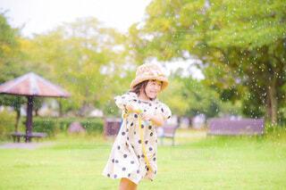 水鉄砲ではしゃぐ麦わら帽子の女の子の写真・画像素材[4756158]
