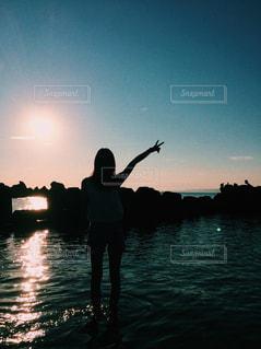 水の体の横に立っている人の写真・画像素材[761743]