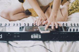 ベッドの上でピアノを弾いている女性 - No.805731