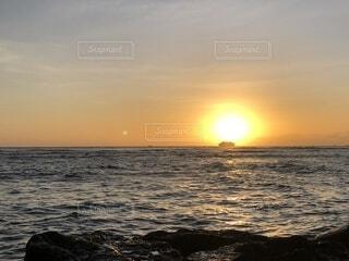 水平線に沈む太陽にシンクロする船の写真・画像素材[4764064]