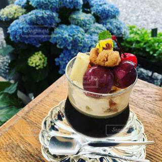 紫陽花をバックに木のテーブル上にあるフルーツパフェ(珈琲ゼリー)の写真・画像素材[4764140]