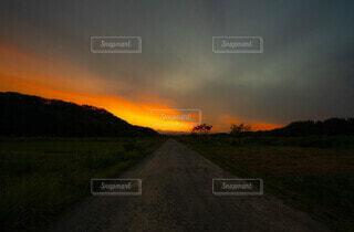 背景に夕日のある道の写真・画像素材[4807041]