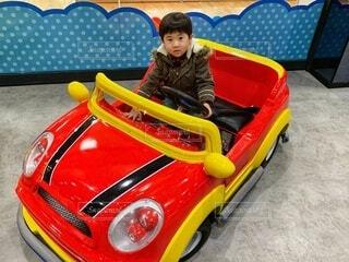 子ども,風景,赤,車,人物,人,自動車,赤ちゃん,おもちゃ,オブジェ,地面,幼児,少年,男の子,ドライブ,運転,遊び場,模型,車両,玩具,グッズ,陸上車両