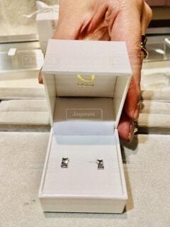 プレゼント用ピアスの宝石ケースにさりげなく添える手の写真・画像素材[4858350]