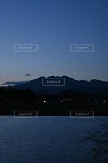 水田と夕日、そびえ立つ山の写真・画像素材[4785866]