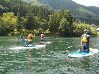 水の中でボートの後ろに乗っている人々のグループの写真・画像素材[4805345]
