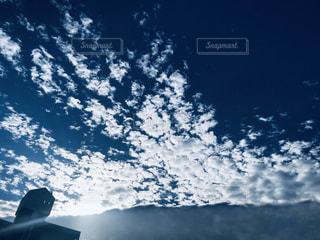 雪に覆われた山の上で空を飛んでいる人の写真・画像素材[2892752]