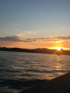 海,空,夕日,小さく漁船