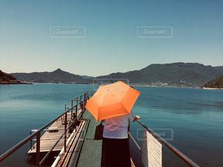 小豆島旅行中、桟橋から傘をさして海のクラゲをみているおばあちゃんの写真・画像素材[2934687]