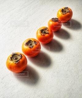 秋の日差しと柿の写真・画像素材[3893050]