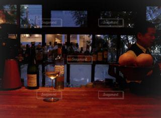 ワインのボトルでテーブルに座っている人々 のグループの写真・画像素材[1627249]