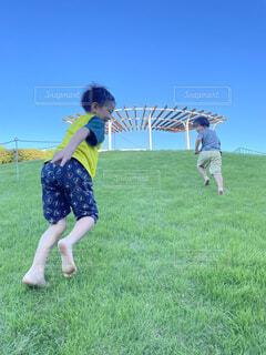 子ども,空,芝生,屋外,青空,景色,走る,草,人物,人,坂道,幼児,男の子,兄弟,若い,弟,遊び場,再生,兄,明るい未来,鬼ごっこ,駆け上がる