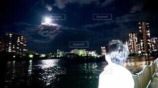 男性,自然,風景,空,夜,暗い,水面,月,月光 月 川 高層 遊歩道 佇む 見とれる サラリーマン,雲 雲に隠れた,若い 中年 青年