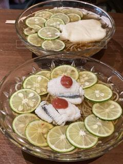 皿に食べ物の皿をトッピングした木製のテーブルの写真・画像素材[4847442]