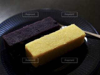 紫色と薩摩芋の羊羹を皿に乗せての写真・画像素材[4923735]