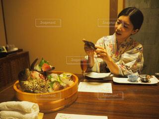 食事のテーブルに座っている女性の写真・画像素材[767335]